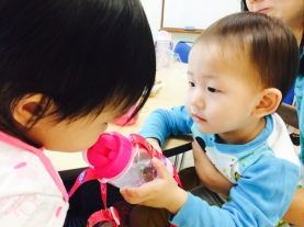 Asher eagerly offering Little E to drink her water.