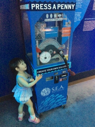 Little E at the press a penny machine