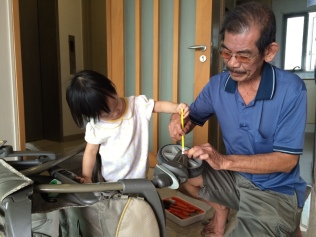 E helping 公公 to hold the pencil