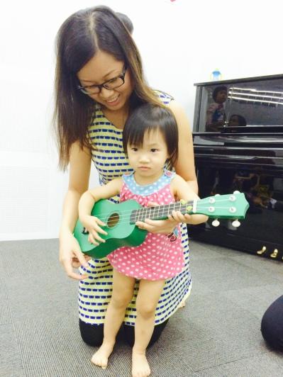 Little E playing a ukulele