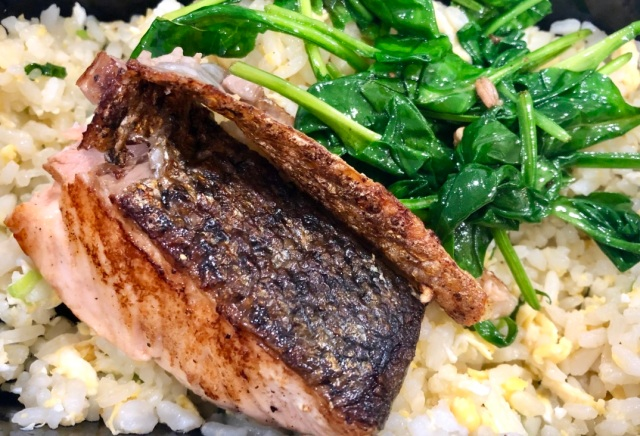 Pan-seared salmon and sautéed spinach on a bed of egg fried rice.
