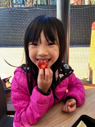 E enjoying her strawberry